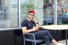One young handsome arabian guy uses and talks on phone, smiles a Stock Images