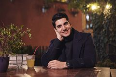 One young handsome man portrait, sitting in cafe garden at table, night sideways, smiling, looking to camera. upper body shot royalty free stock photo