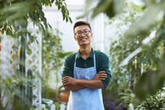 Portrait of one happy young male florist in shop. One Young Happy Asian Male Florist Working in Shop Stock Photography
