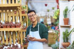 Portrait of one happy young male florist in shop. One Young Happy Asian Male Florist Working in Shop Stock Image