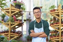 Portrait of one happy young male florist in shop. One Young Happy Asian Male Florist Working in Shop Royalty Free Stock Images