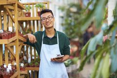 Portrait of one happy young male florist in shop. One Young Happy Asian Male Florist Working in Shop Royalty Free Stock Photography