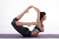 One young healthy sporty caucasian woman exercising yoga on isolated white studio background. Stock Photo