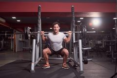 One young man, barbell back squat, dark gym indoor. full lenght. Body shot Royalty Free Stock Image