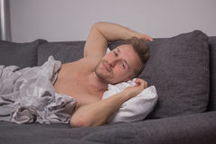 One young man head closeup, bed pillow smiling Royalty Free Stock Photo