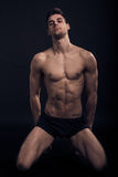 One young man, kneeling sexy handsome abs fit, shirtless body Stock Images