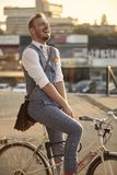 One young man laughing, 20-29 years old, wearing hipster suit, smart casual, sitting on old city bike stock images
