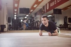 One young man, looking away, plank exercise, gym floor,. Unrecognizable people behind out of focus stock images