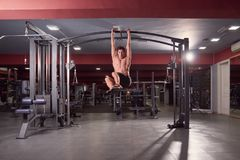 One young man, Multi-Station Gym Machine abs exercise, dark gym. Indoors, full lenght body shot Stock Photos