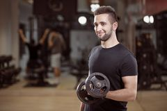 one young man, ordinary average looking, one arm dumbell exercise stock photo