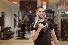 One young man, ordinary average looking, one arm dumbell royalty free stock images