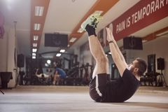 One young man, ordinary average man, exercise abs, arms extended high in air. Sitting on floor, in gym. Unrecognizable people behind out of focus Stock Photography