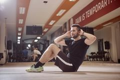 one young man, ordinary average man, exercise abs, sideways, sitting on floor, royalty free stock photography