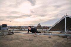 One young man, outdoors workout on rooftop, urban city roofs, rooftops behind, Royalty Free Stock Images