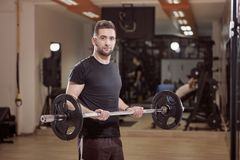 One young man posing, ordinary average looking, holding barbell with weights,. Exercise in gym. Unrecognizable person behind out of focus Royalty Free Stock Images