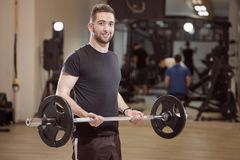 one young man posing, ordinary, average looking, holding barbell with weights, stock image