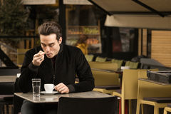 One young man sitting cafe tables coffee cup licking spoon Stock Photo