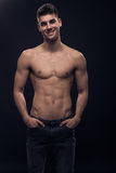 One young man smiling shirtless body jeans Stock Image
