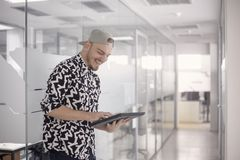 One young man, standing 20-29 years old, casual clothes, smiling laughing, using computer tablet. modern bright white office space stock photos