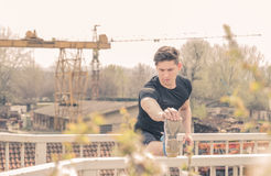 One young man, stretching leg, outdoors, industry tree Stock Photos