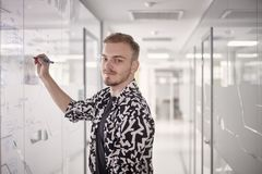 One young man, writing on glass window wall of modern office, with marker, looking to camera stock photography