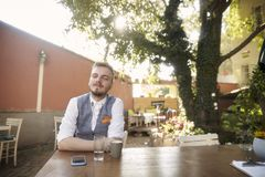 One young man, 20-29 years old, wearing hipster suit, sitting at table in cafe garden, looking to camera, posing with attitude. Confident, head high, looking to royalty free stock photo