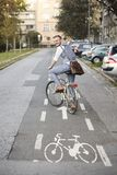 One young man, 20-29 years old, wearing hipster suit, smart casual, looking back to camera, rear view. in city on bike track royalty free stock photo