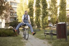 One young man, 20-29 years old, wearing hipster suit, smart casual, ridiculous funny riding bike legs spread in park road trail royalty free stock photo