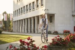 One young man, 20-29 years old, wearing hipster suit, smart casual, riding cycling old city bike, sunny day outdoors stock photos