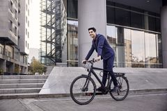 One young man, 20-29 years old, wearing suit, looking smiling. riding, pedaling standing, fancy bicycle. full length body. modern royalty free stock images