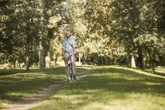 One young man, 20-29 years, riding bicycle in park trail outdoors. looking sideways, enjoying happy stock images