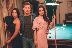 One young man stand beyween two models. They look on camera seriously. Young women hold billiard cues in hands. They stand in. One young men stand beyween two stock photo