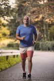 One young overweight man, outdoors nature, running on asphalt road royalty free stock images