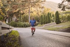 One young overweight man, outdoors nature, running on asphalt road stock photo