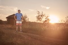 One young overweight man, 30-35 years, proud, posing standing, golden orange sunset,. Sun, outdoors nature landscape, rural area stock photography