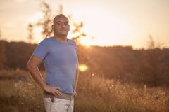 One young overweight man, 30-35 years, proud, posing standing,. Golden orange sunset, sun, outdoors nature landscape, rural area royalty free stock photo