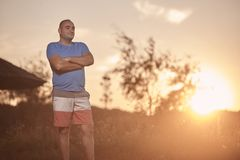 One young overweight man, 30-35 years, proud, posing standing,. Golden orange sunset, sun, outdoors nature landscape, rural area stock photos