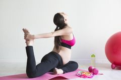 One young pregnant woman doing fitness exercises Stock Photo