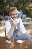 One young smiling man, head nod gesture, 20-29 years old, wearing hipster suit, sitting at table in cafe garden, looking to. Camera, drinking espresso from royalty free stock photos