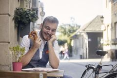 One young smiling man, 20-29 years old, wearing hipster suit, siting on street, eating pretzel in front of bakery outdoors. acting royalty free stock images