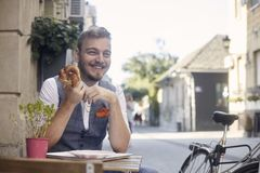 One young smiling man, 20-29 years old, wearing hipster suit, siting on street, eating pretzel in front of bakery outdoors. acting royalty free stock photo