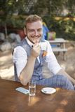 One young smiling man, 20-29 years old, wearing hipster suit, sitting at table in cafe garden, looking to camera, drinking royalty free stock images