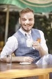 One young smiling man, 20-29 years old, wearing hipster suit, sitting at table in cafe garden, looking to camera, posing with stock photo