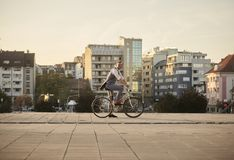 One young smiling man, 20-29 years old, wearing hipster suit, smart casual, sitting on old city bike. city buildings panorama stock image