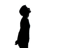 One young teenager boy or girl looking up silhouette. One caucasian young teenager silhouette boy or girl looking up portrait in studio cut out isolated on white Stock Image