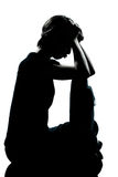 One young teenager boy or girl pouting sadness silhouette. One  young teenager silhouette boy or girl pouting sadness full length in studio cut out isolated on Stock Photo