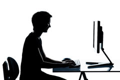 One young teenager boy or girl silhouette computer computing typ Royalty Free Stock Image