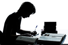 One young teenager boy or girl silhouette studying reading books Royalty Free Stock Photos