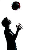 One young teenager boy  girl silhouette tossing soccer football Stock Photo