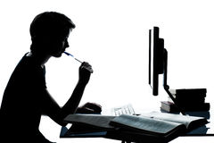 One young teenager boy girl studying with computer. One caucasian young teenager silhouette boy or girl studying with computer computing laptop in studio cut out Stock Photo